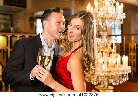 Couple, man and woman, drinking champagne in a fine dining restaurant, each with glass of sparkling wine in hand, a large chandelier is in Background