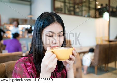 Beautiful Asian Women Hold Hot Latte Art Coffe Cup Sitting In Cafe