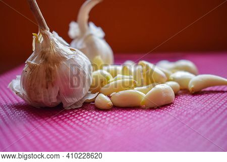 Stock Photo Of Fresh Organic Unpeeled Garlic With Peeled Garlic Bulbs Decorated On Purple Color Chop