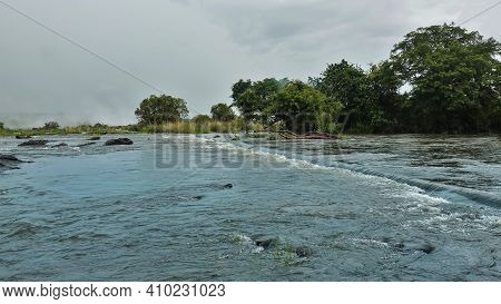 The Zambezi River Flows Towards The Edge Of The Abyss. Stones And Branches Of Trees Lie In The River