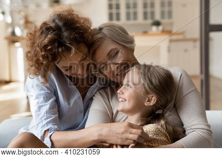 Three Generation Family Little Girl Mom Grandma Tickle On Sofa