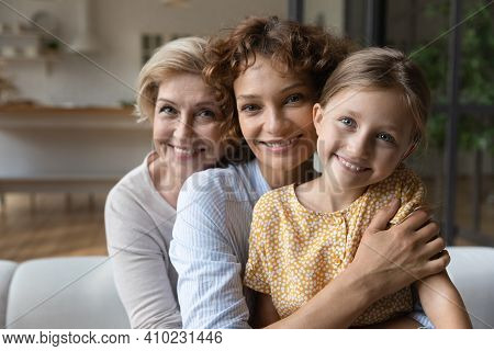 Intergenerational Family Dynasty Of Three Diverse Women Cuddle On Sofa