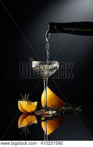 Gin Is Poured In A Small Glass From An Antique Bottle Of Dark Glass. A Strong Alcoholic Drink With L