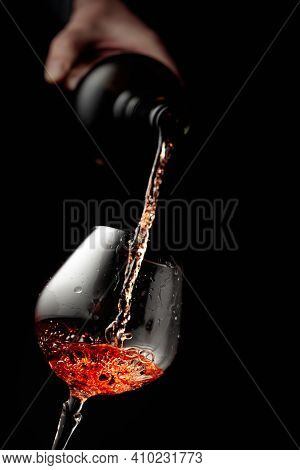 Pouring Brandy In A Glass Goblet. Black Background With Copy Space.