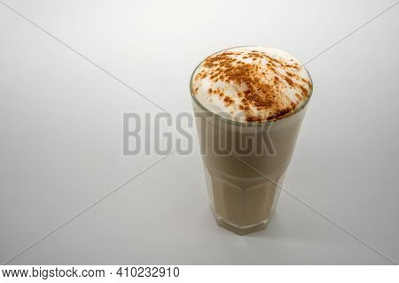 Latte Coffee With Milky Foam Sprinkle With Cocoa Power For Decoration In Double Wall Glass Isolated