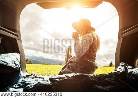 Girl resting in her car, journey made by car. Woman hiker, backpacker traveler camper in sleeping bag, relaxing, drinking hot tea on top of mountain. Road trip. Health care, authenticity,