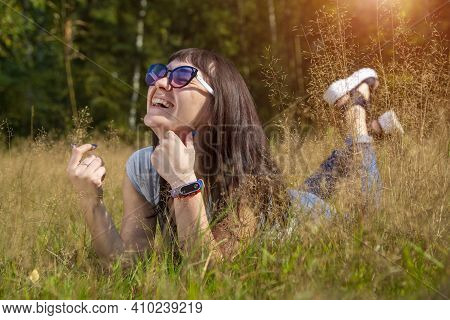Happy Beautiful Young Woman In Sunglasses Smiles And Lies On A Meadow In The Grass In The Sunshine E