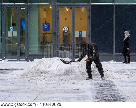 Moscow. Russia. February 12, 2021. A Utility Worker Shovels Snow With A Shovel On A City Street Duri