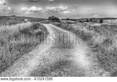 Dirt Road Crossing Dry Fields In The Countryside In Tuscany, Italy. Concept For Agriculture And Farm