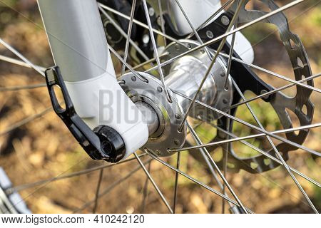 Front Bicycle Hub With A Visible Caliper, Spokes And A Brake Disc.
