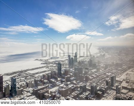 Aerial Elevated View Looking Out Of The Chicago South Loop And Lake Michigan Covered In Snow After A