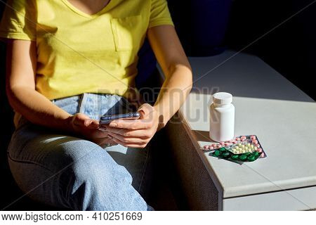 Unrecognizable Woman Sitting On Sofa With Blister Pack Of Pills Using Online Pharmacy Store
