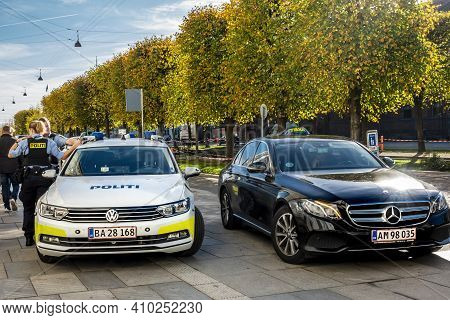 Copenhagen, Denmark - Oct 19, 2018: Police Officers Beside Their Vehicle. A Taxi Parked Beside It. B