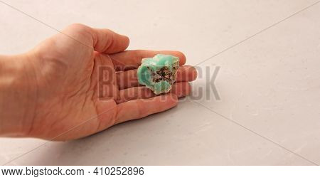 Natural Chrysoprase Stone Is On A Woman's Hand, In The Palm Of Her Hand, On A Light Background. Natu