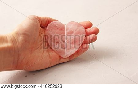 Natural Rose Quartz Heart Stone Is On A Woman's Hand, In The Palm Of Her Hand, On A Light Background