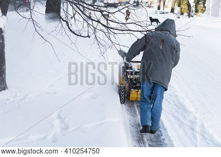 Man Cleaning Driveway With Snow Machines After A Snow Storm. Snow Removal Equipment Working On The S