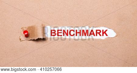 Beneath The Torn Strip Of Kraft Paper Attached With A Red Button Is A White Paper Labeled Benchmark