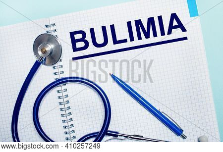 On A Light Blue Background, An Open Notebook With The Word Bulimia, A Blue Pen And A Stethoscope. Vi