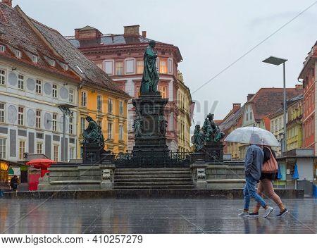Graz/austria - June 22, 2020: People With Umbrella Passing By Erzherzog Johann Fountain At Hauptplat