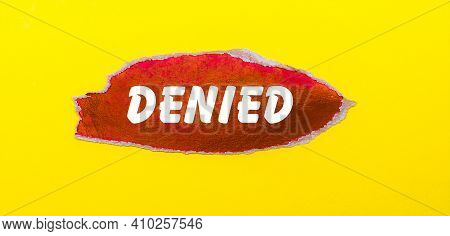 On A Yellow Background, A Sheet Of Red Paper With The Word Denied