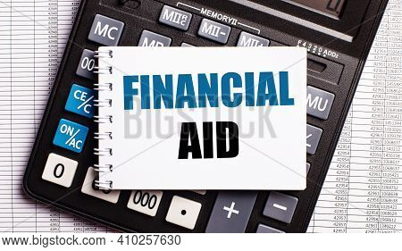 On The Table Are Reports, A Calculator And A Card With The Words Financial Aid On It. Business Conce
