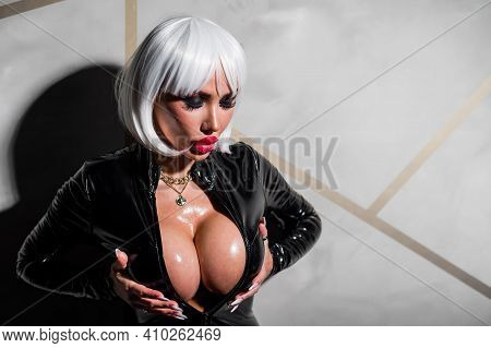 Sexy Woman In A Blonde Wig And Latex Catsuit. Girl With Big Fake Tits