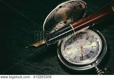Beautiful Pocket Watch And Fountain Pen Close Up On A Black Wooden Table