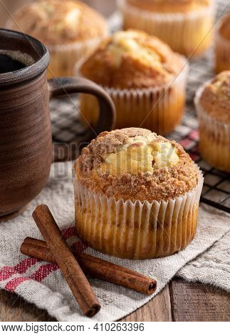 Cinnamon Muffin Next To Coffee Mug With Muffins On A Wire Rack In Background