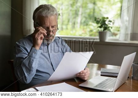 Focused Mature Man Reading Financial Document Or Received Paper