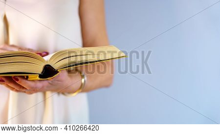 Woman Holding A Book And Reading In Standing Posture On Blue Background With Copy Space. Concept, Re