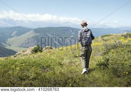 Woman With Backpack Hiking In Mountains.  Hiking Active People Lifestyle Wearing Backpack Exercising