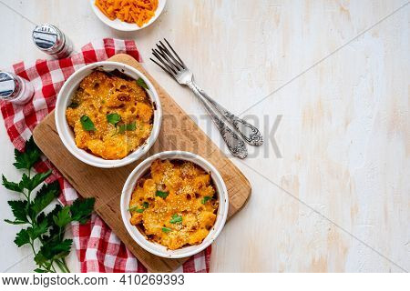 Two Servings Of Mac And Cheese, Macaroni In Cheese Sauce, In White Ceramic Frames On A Light Concret