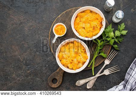 Two Servings Of Mac And Cheese, Macaroni In Cheese Sauce, In White Ceramic Frames On A Black Concret