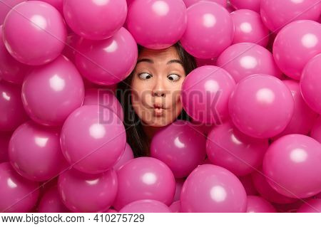 Funny Childish Young Asian Woman Makes Fish Lips Crosses Eyes Foolishes Around While Decorating Hall