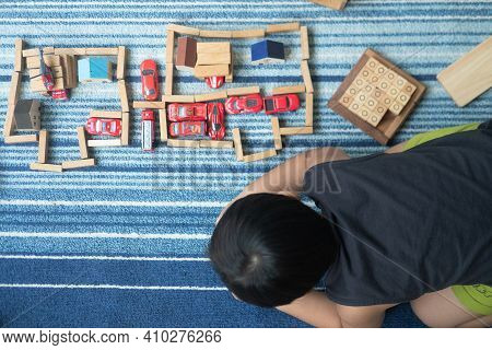 Bangkok, Thailand - February 28, 2021 : Child Playing With Miniature Toy Cars And Wood Block. Family