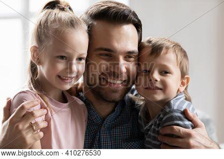 Candid Portrait Of Happy Best Dad Embracing Two Preschooler Kids
