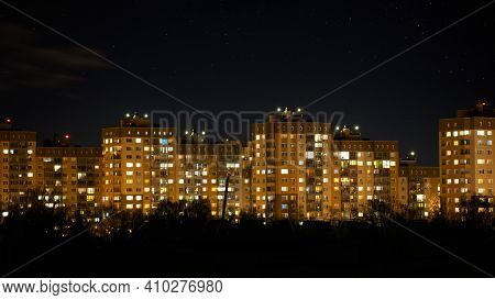 The Night View On Residential Buildings Area. Apartment Building Windows At Night Time.