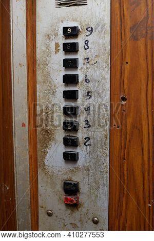 Old Elevator Buttons Against Wooden Panels Inside A Vintage Elevator