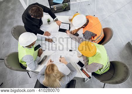 Top View Of Four Men And One Woman Sitting Together At Table And Discussing Blueprints During Busine