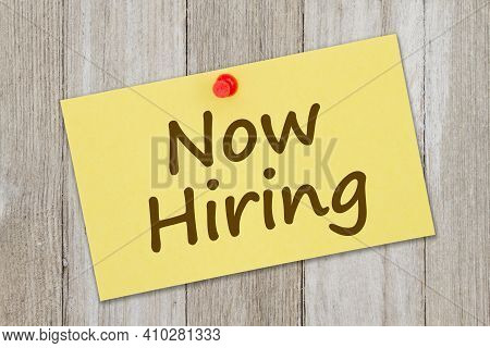 Now Hiring Message On Retro Yellow Paper Index Card With Pushpin On Weathered Wood
