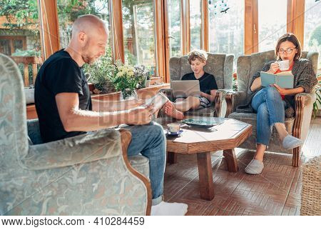 Mother, Father And Son Family Sitting Together In Sunroom In Cozy Armchairs And Reading Books, Using