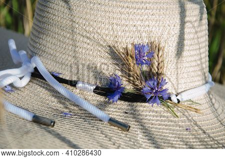 Purple Lupine Flowers Covered With Straw Hat In Field. Hat Near A Bouquet Of Lupine Flowers On Morni