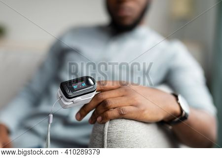 Unrecognizable African Guy With Pulse Oximeter Clip On Hand Measuring Oxygen Saturation Level Monito