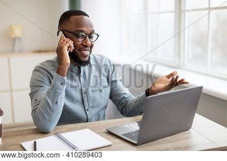 Positive Black Businessman Talking On Mobile Phone Sitting At Laptop Computer At Workplace In Modern