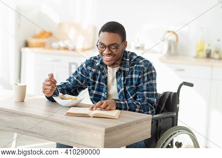 Positive Black Impaired Guy In Wheelchair Having Breakfast And Reading Interesting Book At Kitchen.