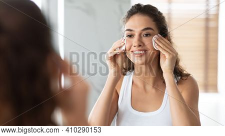 Facial Skin Care. Young Woman Using Cotton Pads Removing Makeup And Circles Under Eyes Caring For Fa