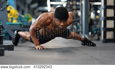 Push-up, Press-up At Gym Concept. Motivated Black Guy Bodybuilder Doing Some Push-ups With One Hand