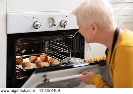 Over Shoulder Shot Of Senior Grey-haired Woman With Short Hair Checking Beautiful Croissants In Oven