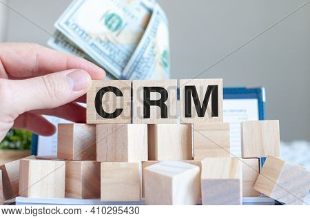 The Word Crm On The Wooden Blocks And A Money In The Background, Business Concept. Crm - Short For C