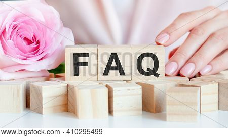 A Woman Holds A Wooden Cube With The Text Of Faq In Her Hand. On The Wooden Cubes There Is A Living